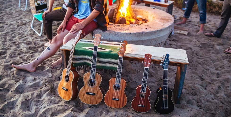 Na areia da praia, encostados num banco, cinco ukuleles de tamanhos diversos. Atrás uma fogueira, pessoas e cadeiras de praia.