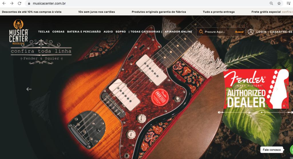 Página home do site da Musica Center. No topo do site estão as categorias Teclas, Cordas, Bateria e Percussão, Áudio, Sopro, Todas as Categorias e Afinador Online. Abaixo uma foto de uma guitarra Fender Jaguar na cor sunburst.